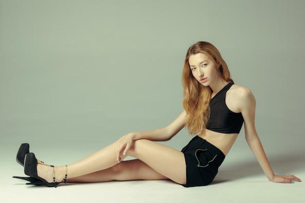 床に座っている若いきれいな女性