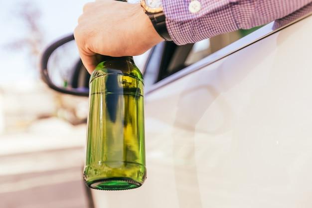 車を運転中にアルコールを飲む男性