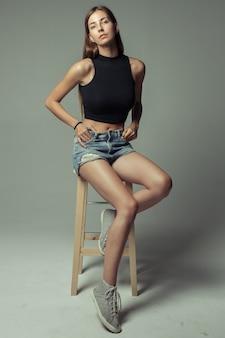 スツールに座っている若いきれいな女性