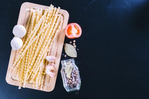 黒い木製の背景、トップビューで生スパゲッティ