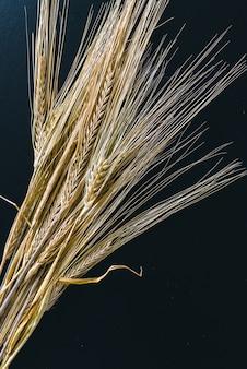 Колоски пшеницы на черной деревянной поверхности