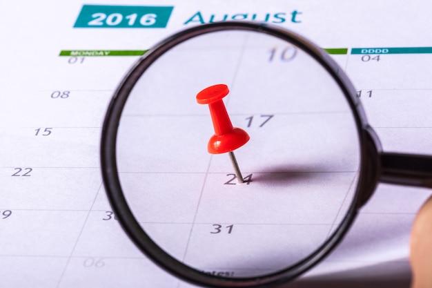 赤い押しピンでカレンダーをズームする虫眼鏡