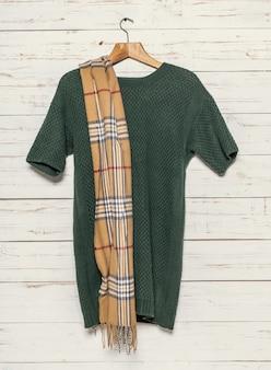 木製ラックのニットセーターとスカーフ