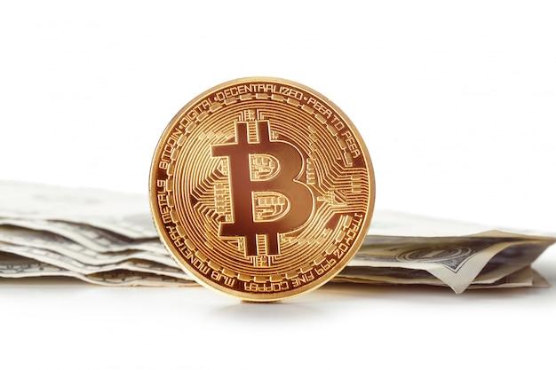 Блестящий золотой биткойн и долларовые купюры
