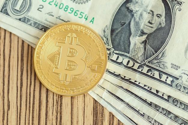 Золотая монета биткойн и однодолларовая банкнота