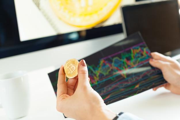 黄金のビットコインを持っている手