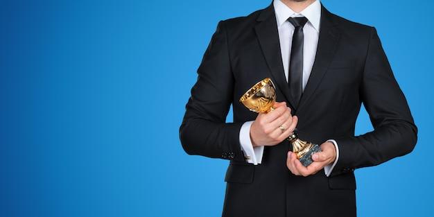 До неузнаваемости бизнесмен с золотым трофеем. концепция успеха