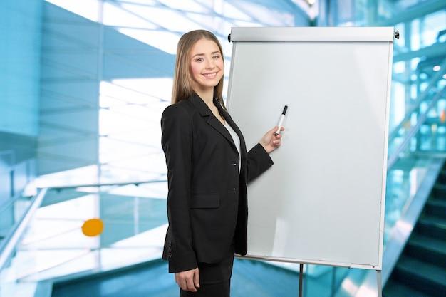 Деловая женщина объясняет на доске