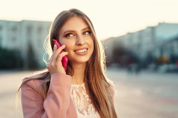 Крупным планом портрет молодой женщины, говорить по телефону на улице
