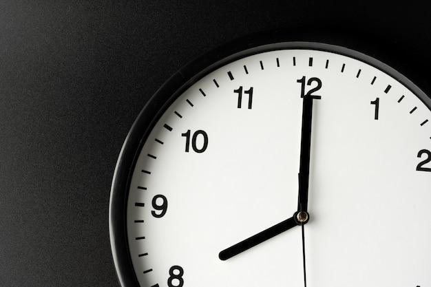 目覚まし時計は黒い壁にクローズアップ