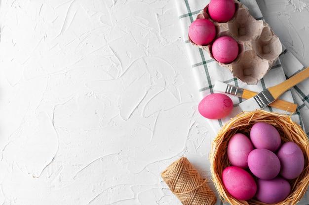 白いテーブルにピンクでイースターエッグを塗る、上からの眺め