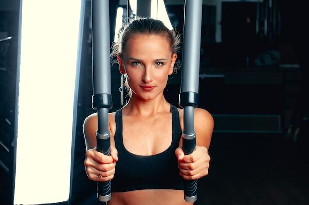 トレーニングマシンで腕のための演習を行う若い魅力的な女性