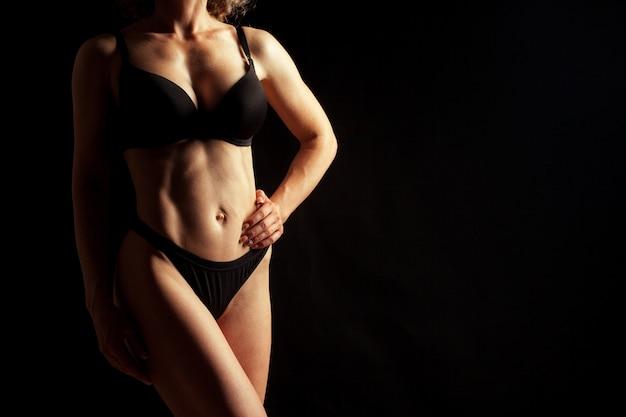 黒い壁に分離された裸の美しい少女
