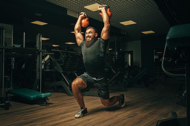 暗いジムでダンベル体操を行うボディービルダー
