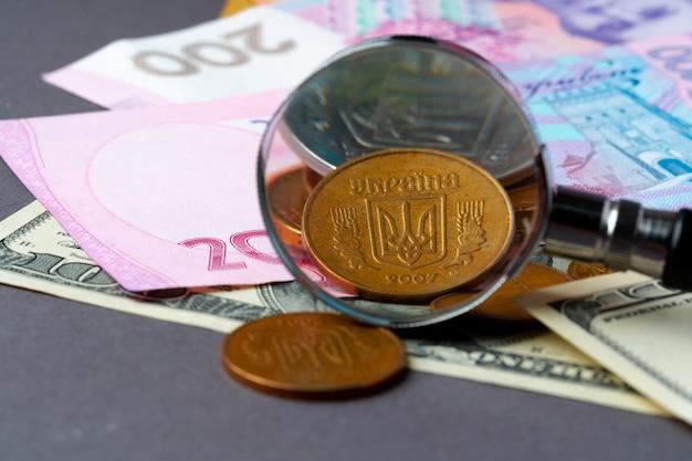 ウクライナのグリブナと米ドル紙幣の虫眼鏡。為替レートの概念