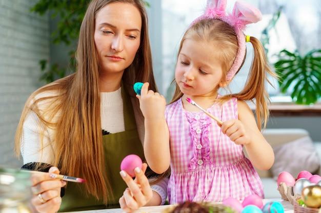 かわいい家族、母と娘のイースターのお祝いの準備