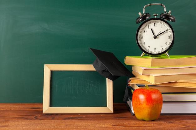 Снова в школу - яблоко и книги с карандашами и доской