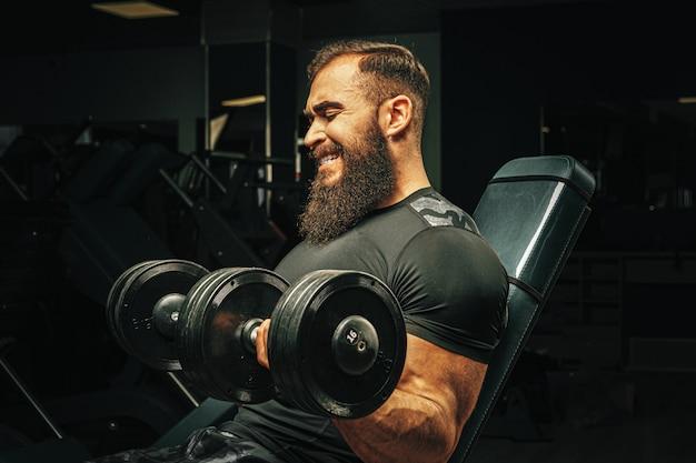 ジムでダンベルを持ち上げるスポーツ体を持つ男性