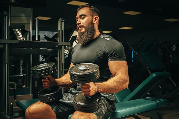 暗いジムでウェイトを持ち上げる筋肉の若い男