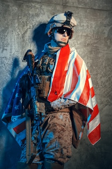 Человек военного снаряжения наемного солдата в наше время с флагом сша в студии