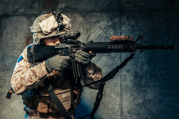 Молодой человек в военной форме наемного солдата в наше время на темном фоне в студии