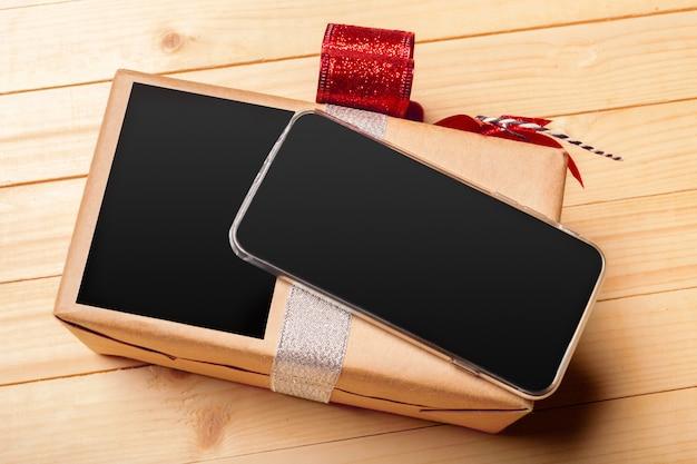 スマートフォンと木製の背景のギフト