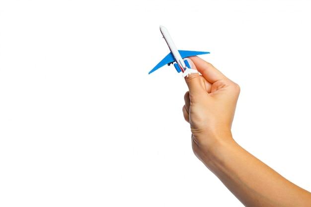 白い背景で隔離の飛行機グッズモデルを持っている手