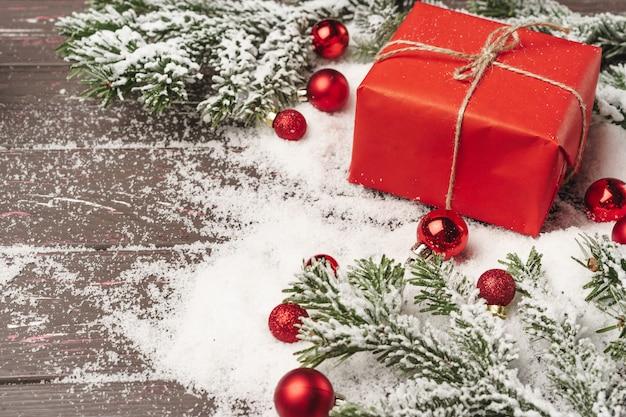 雪で覆われた木製のテーブルの上のクリスマスプレゼント