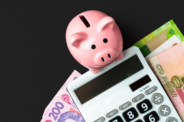貯金箱とウクライナグリブナとロシアルーブルのお金のノートを持つ電卓