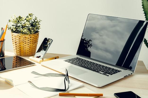 事務用品と作業テーブルの明るい部屋でのノートパソコン