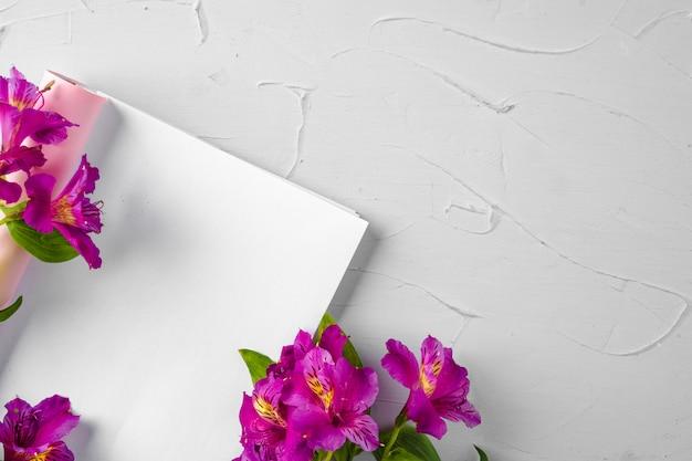 生花で飾られた雑誌のページのモックアップ