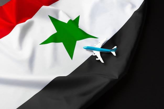 シリアの布旗の上に小さなおもちゃの飛行機