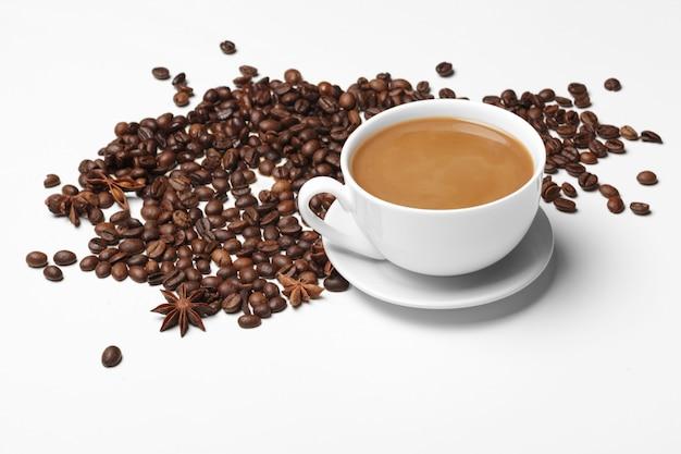白で隔離されるコーヒー豆のコーヒー豆の小さなカップ