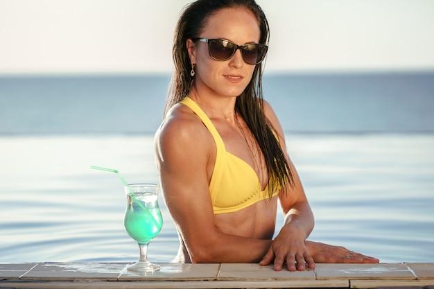 Среднего возраста женщина отдыхает в воде бассейна