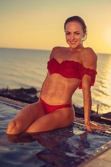 プールの水に赤いビキニで中年の女性
