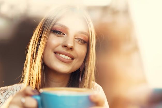 一杯のコーヒーを飲んで、窓から見ている若い女性の肖像画