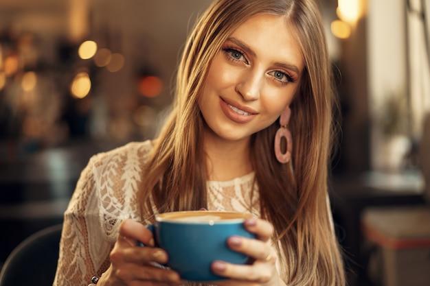 彼女の飲み物を楽しんでいるコーヒーショップに座っている美しい若い女性