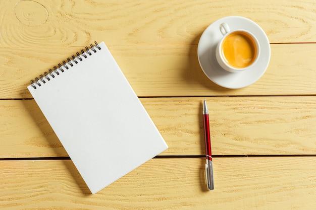上面図。コーヒーとコーヒーカップ。空白のノートブックを置くペン。