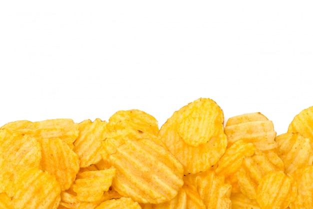 白で隔離される黄色のポテトチップス