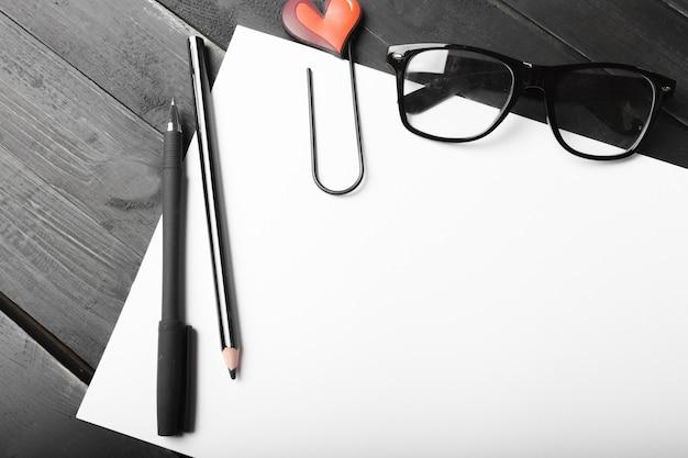 空白のノートブックと木製のテーブルにグラスと鉛筆