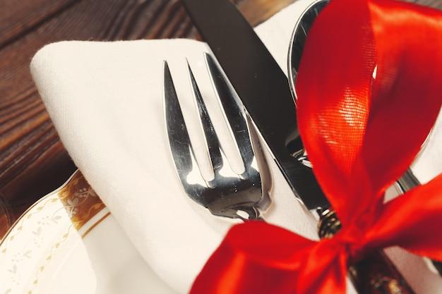装飾が施された美しい赤いクリスマステーブルの設定をクローズアップ