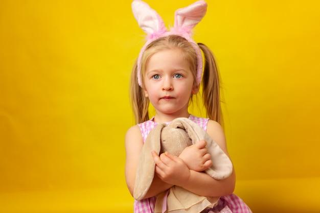 Пасхальная концепция. малышка блондинка счастливая девушка с ушками зайчика
