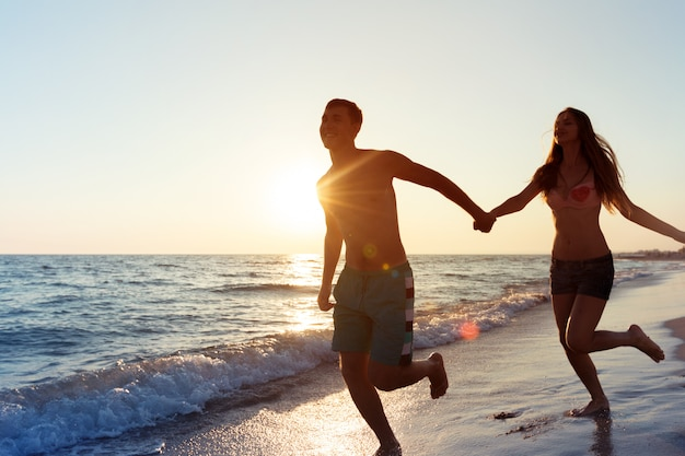 海を楽しんで幸せな若いカップル