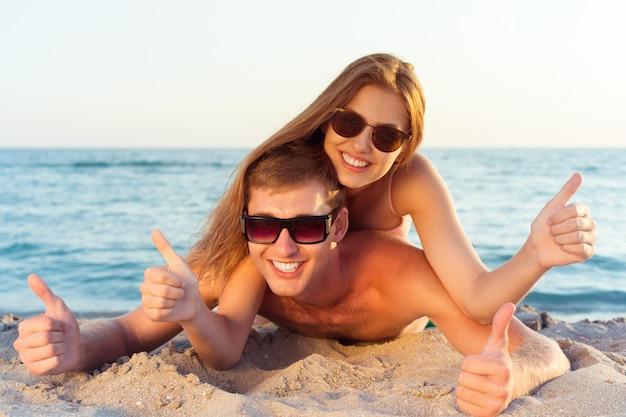Счастливая пара в солнцезащитных очках на пляже