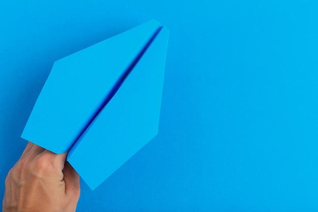 人間の手で保持している紙飛行機。旅行と観光の概念