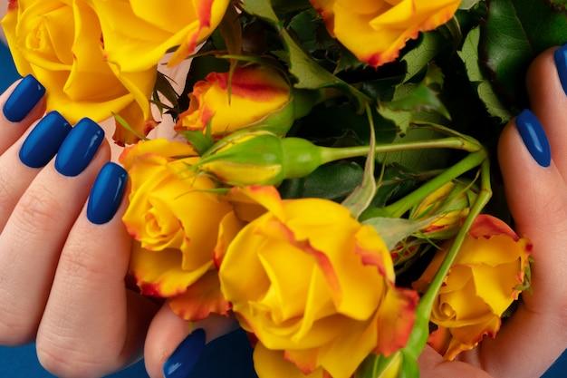 Красивые руки женщины с маникюром, держа розы на классическом синем фоне