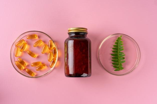 ピンクの背景にハーブとハーブの栄養補助食品トップビュー