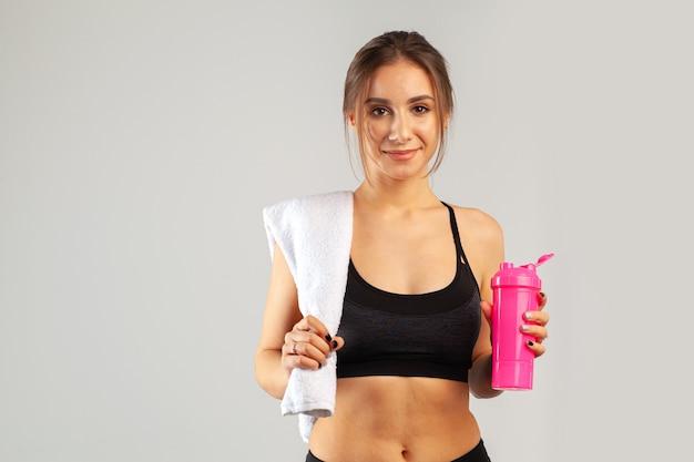 Красивая молодая спортивная женщина позирует с полотенцем на шее на сером фоне