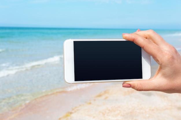 ビーチでスマートフォンを使用して美しい女性の手