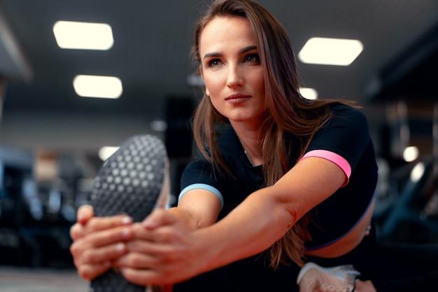 Подходит женщина делает упражнения на растяжку для ног
